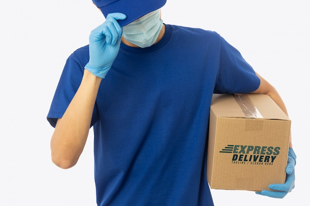 Delivery man hand in medical gloves and wearing mask holding cardboard box mockup template.