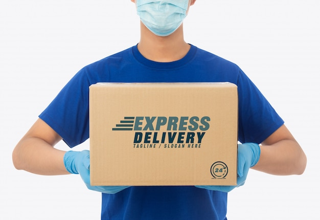 Delivery man hand in medical gloves and wearing mask holding cardboard box mockup