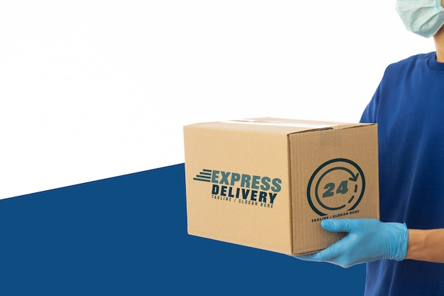 Delivery man hand and wearing medical mask holding cardboard boxes mockup. delivery service concept