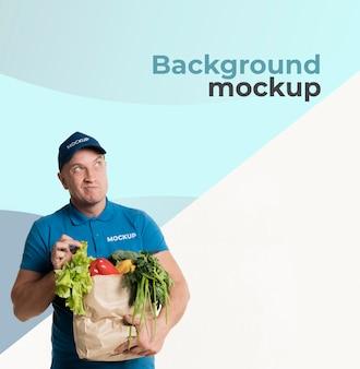 背景のモックアップと食料品の袋を保持している配達人