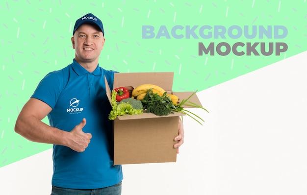 背景のモックアップと野菜がいっぱい入った箱を持って配達人