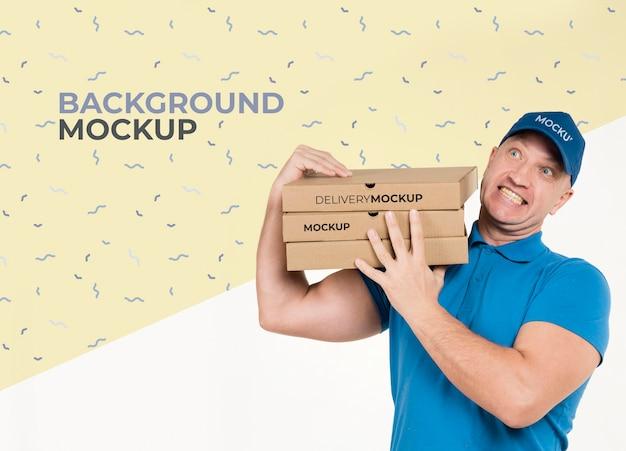 背景のモックアップとピザの箱の束を持って配達人