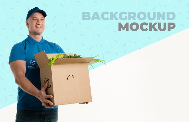 Delivery man holding a box full of vegetables