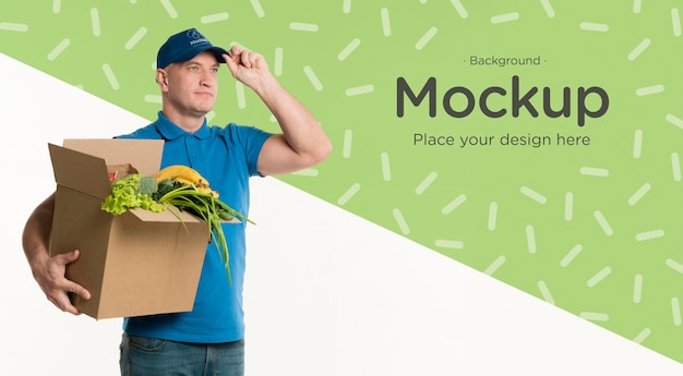 Delivery man holding a box of vegetables