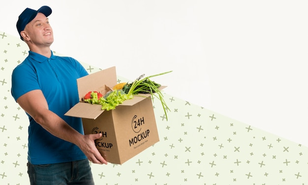 Delivery man holding a box with different vegetables with copy space