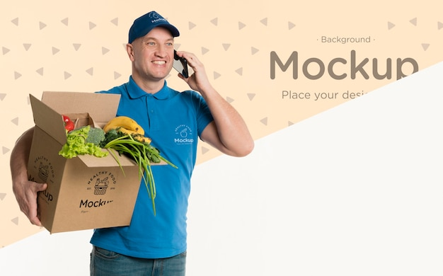 Delivery man holding a box with vegetables