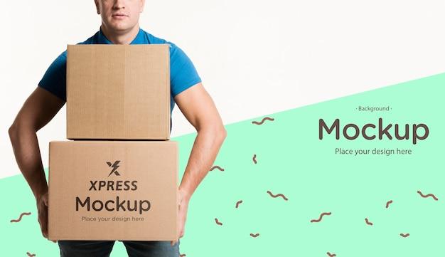 Uomo di consegna che tiene un mazzo di scatole mock-up