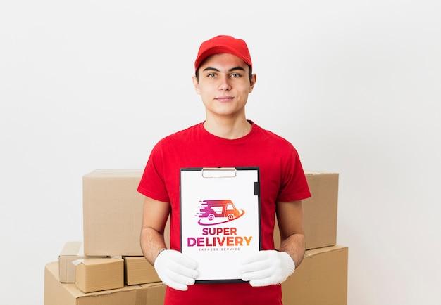 Доставка человек с буфером обмена возле макетов посылок