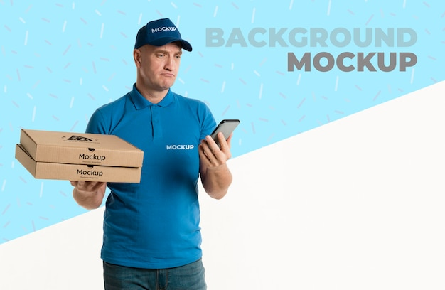 Delivery man holding some pizza boxes while looking sad at his phone