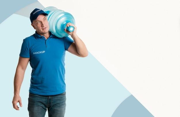 Uomo di consegna che tiene una bottiglia d'acqua