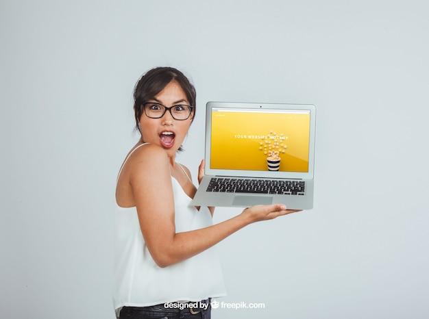 驚くべき女性とラップトップとのモックアップのデザイン