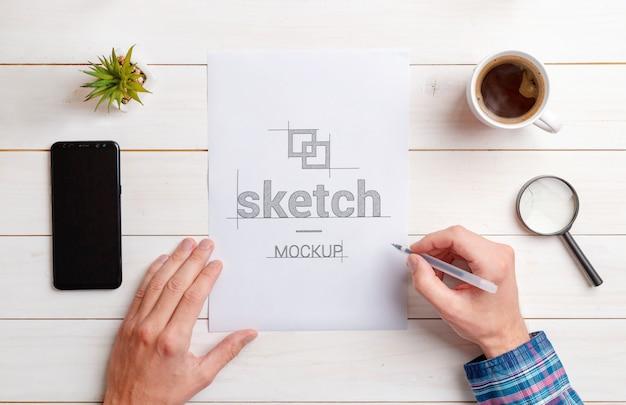 Дизайнерский эскиз макета. вид сверху, плоский лежал состав бумаги на рабочий стол. телефон, кружка кофе, завод; лупа рядом. белый деревянный стол