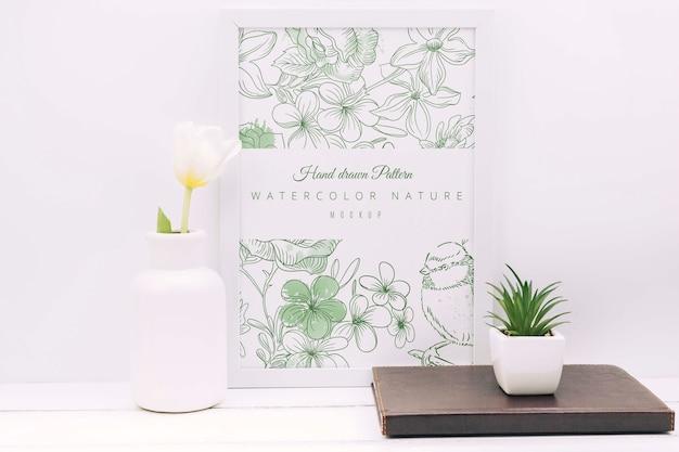 Composizione da scrivania con decoro floreale e cornice mockup