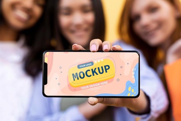 Различные красивые женщины держат макет смартфона