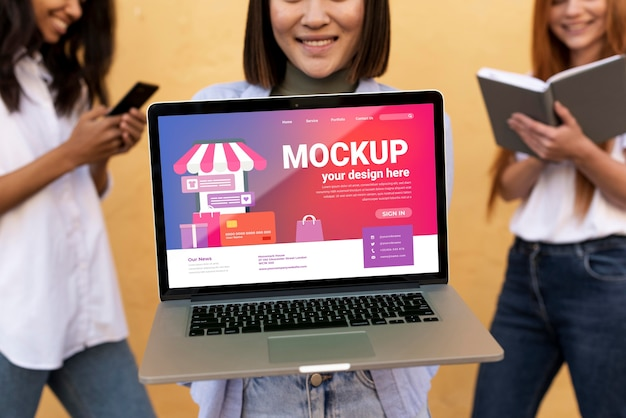 Different beautiful women holding a laptop mock-up