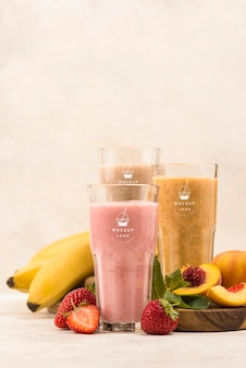 Different fruit summer smoothies in glasses front view