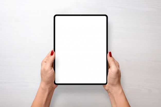 Digital tablet mockup in woman hands top view vertical position