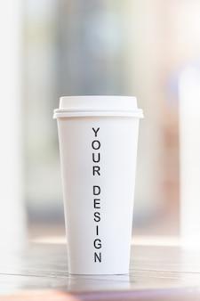 使い捨てのコーヒーカップとカフェのテラスで木製のテーブルの上のスマートフォンぼやけて背景
