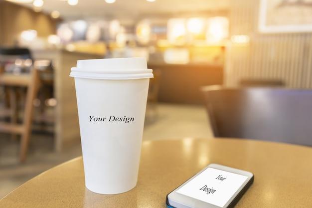 スマートフォンでコーヒーショップのバックグラウンドで木製のテーブルの上の使い捨てのホットコーヒーカップ