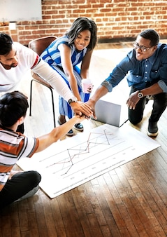 Diverse team stacking hands over a project plan mockup