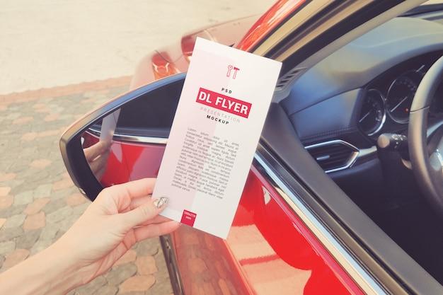 Рекламный флаер dl в руке возле макета автомобиля