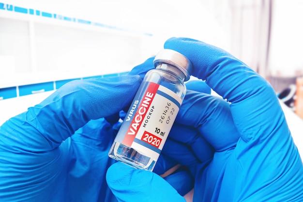 의료 장갑에 의사는 백신 병 모형을 보유하고