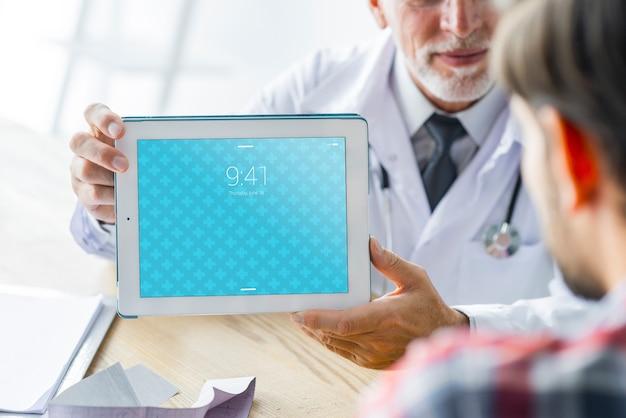 患者にタブレットを示す医者