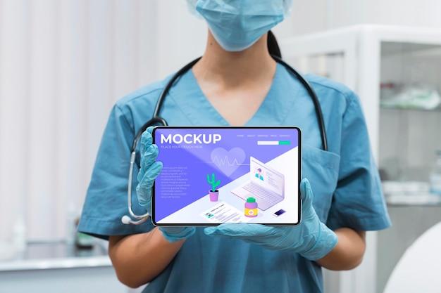 タブレットのモックアップを保持しているフェイスマスクを持つ医師
