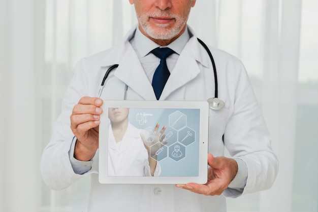 Doctor with stethoscope holding a tablet