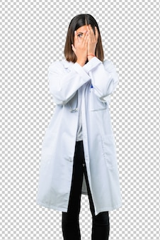 Doctor woman with stethoscope covering eyes by hands and looking through the fingers