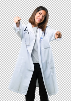 Doctor woman with stethoscope points finger at you while smiling