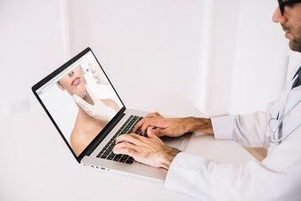 医者はラップトップで働いています