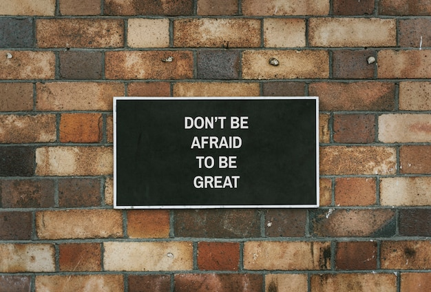 Don' be afraid to be great board mockup on a brick wall