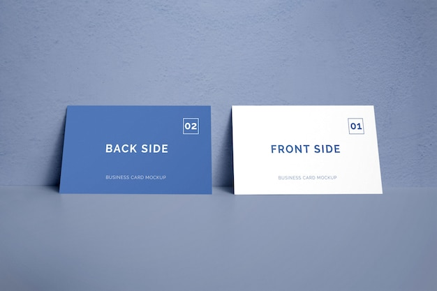 Double sided business card laying on a wall mockup