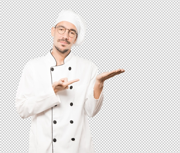 Doubtful young chef holding something with his hand