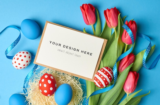 Easter holiday greeting card mockup with colored eggs, ribbons and red tulip flowers on blue