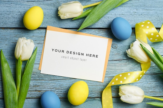 Easter holiday greeting card mockup with colored eggs, ribbons and tulips