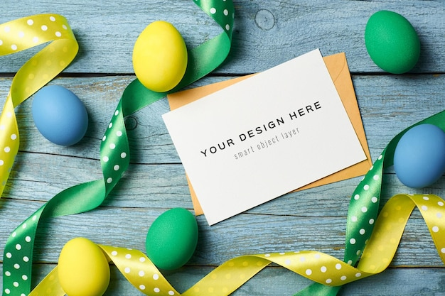 Easter holiday greeting card mockup with colored eggs and ribbons on wooden table