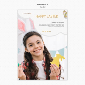 Modello del manifesto di pasqua con il bambino che tiene le forme del coniglietto