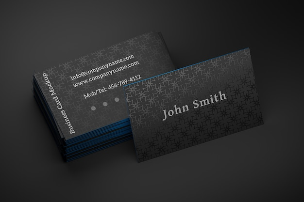 Editable mock up of a stack of black business cards with one standing card on black