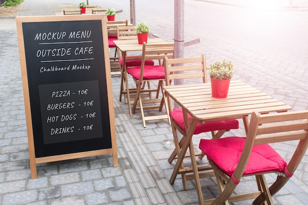Editable psd mockup template of summer outside cafe black menu board with wooden tables and chairs.