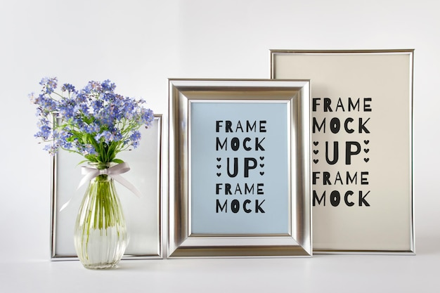 Editable psd mockup template with composition of three silver frames and blue flowers