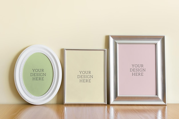 Editable psd mockup template with three silver a4 a5 and oval frame on wooden surface