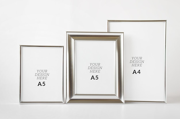 Editable psd mockup template with three silver metallic blank frames on white background.