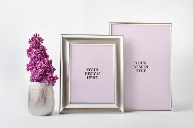 두 개의 은색 빈 프레임과 분홍색 라일락이 있는 은색 꽃병이 있는 편집 가능한 psd 모형 템플릿.