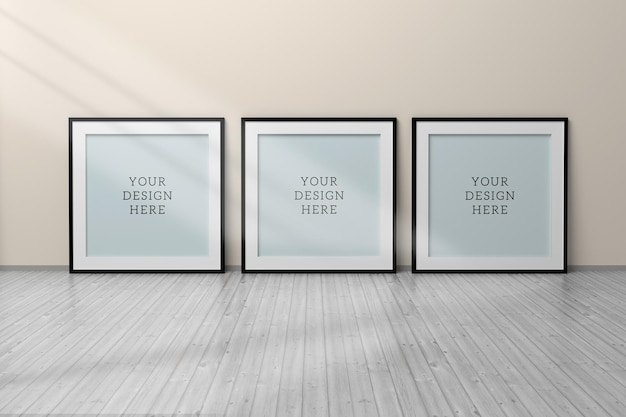 Editable psd mockup with three black square blank frames standing on wooden floor next to wall