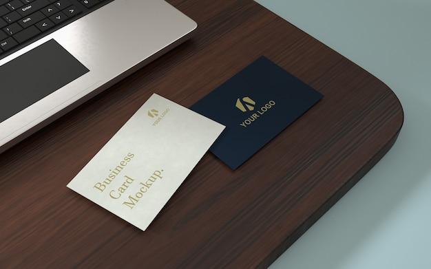 ノートパソコンとテーブルの上のエレガントな名刺のモックアップ