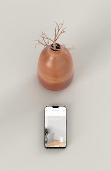 モックアップスマートフォンと花瓶でエレガントな構成