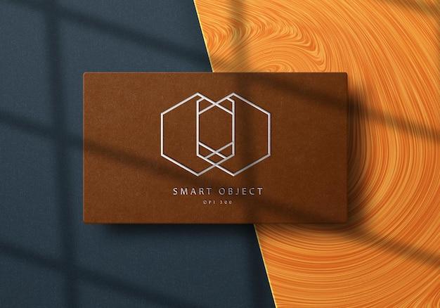 Elegant logo mockup design on business card with silver foil effect