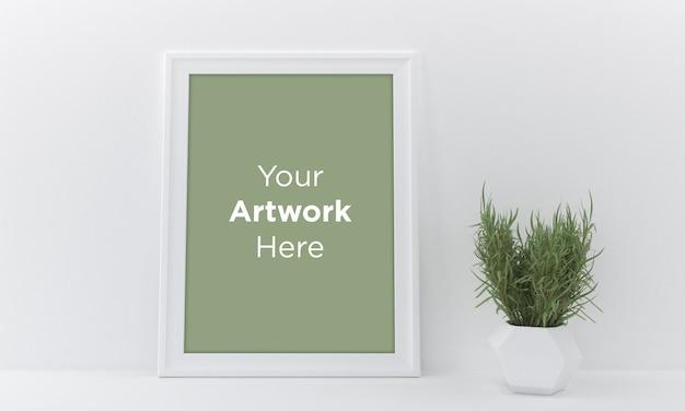 Пустая рамка для фотографий на белой стене с вазой и растением